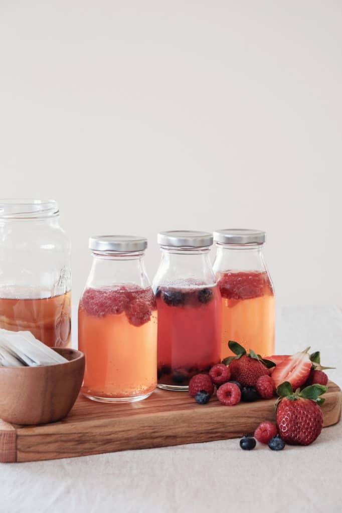 Three bottles of kombucha flavored with different berries on a wooden serving board