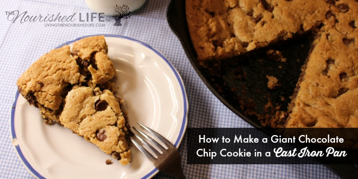 A yummy chocolate chip cookie slice from a giant cookie in a cast iron pan