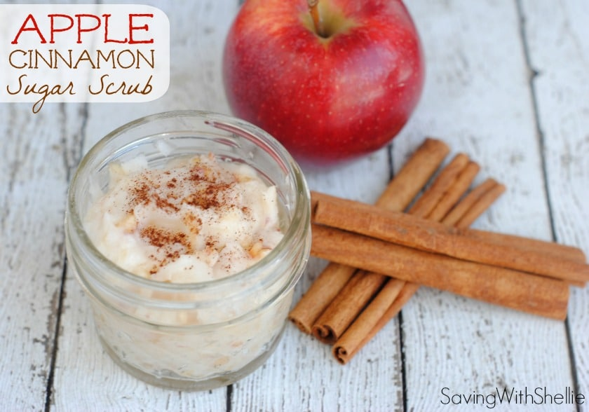 a red apple and cinnamon sticks on a table with a jar of apple pie sugar scrub