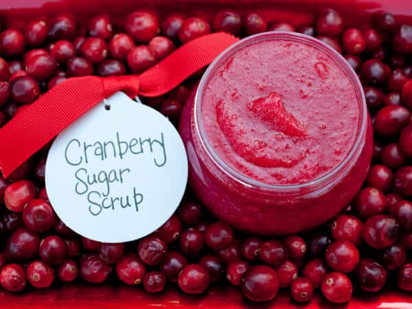 crimson cranberry sugar scrub in a jar on a bed of fresh cranberries