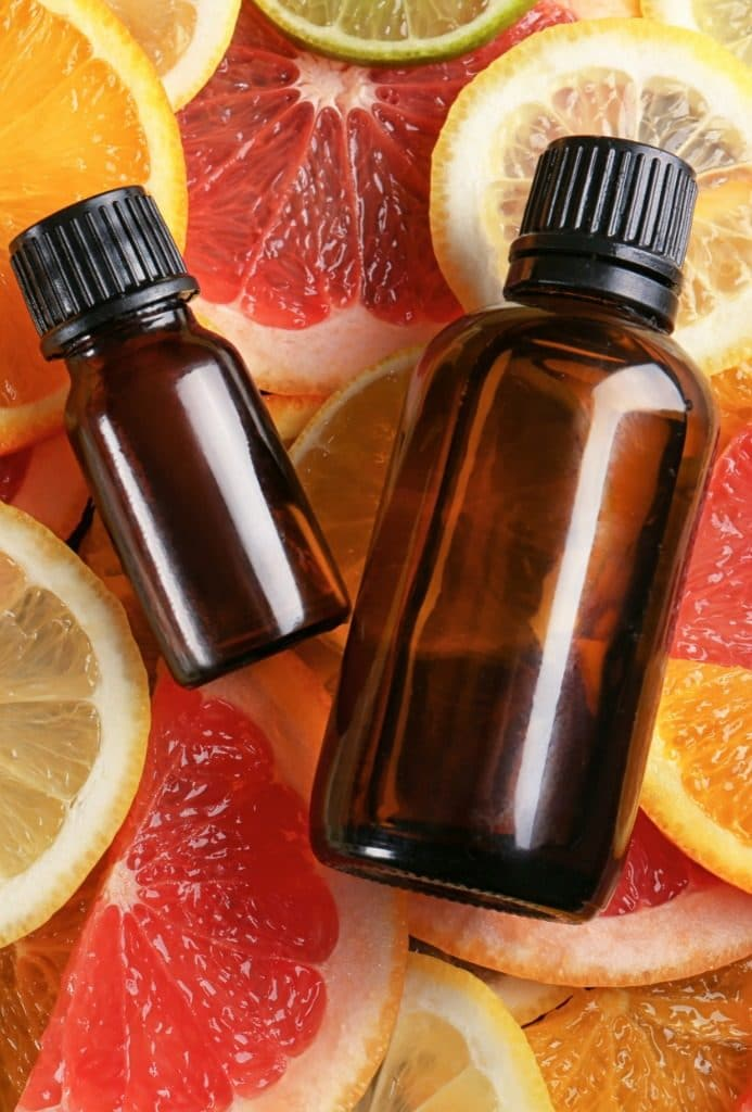 Two amber essential oil bottles on a background of citrus fruit slices