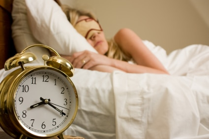 Blond woman sleeping in bed with eye cover on with focus on the alarm clock time being after eight o'clock
