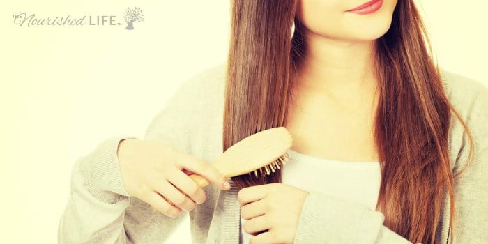 Woman brushing strong, healthy hair with a natural brush