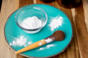 simple face powder on a blue plate with a makeup brush