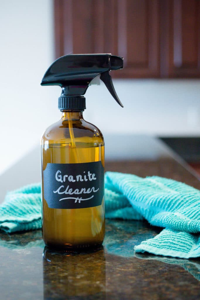 An amber glass spray bottle of homemade granite cleaner on a dark granite counter