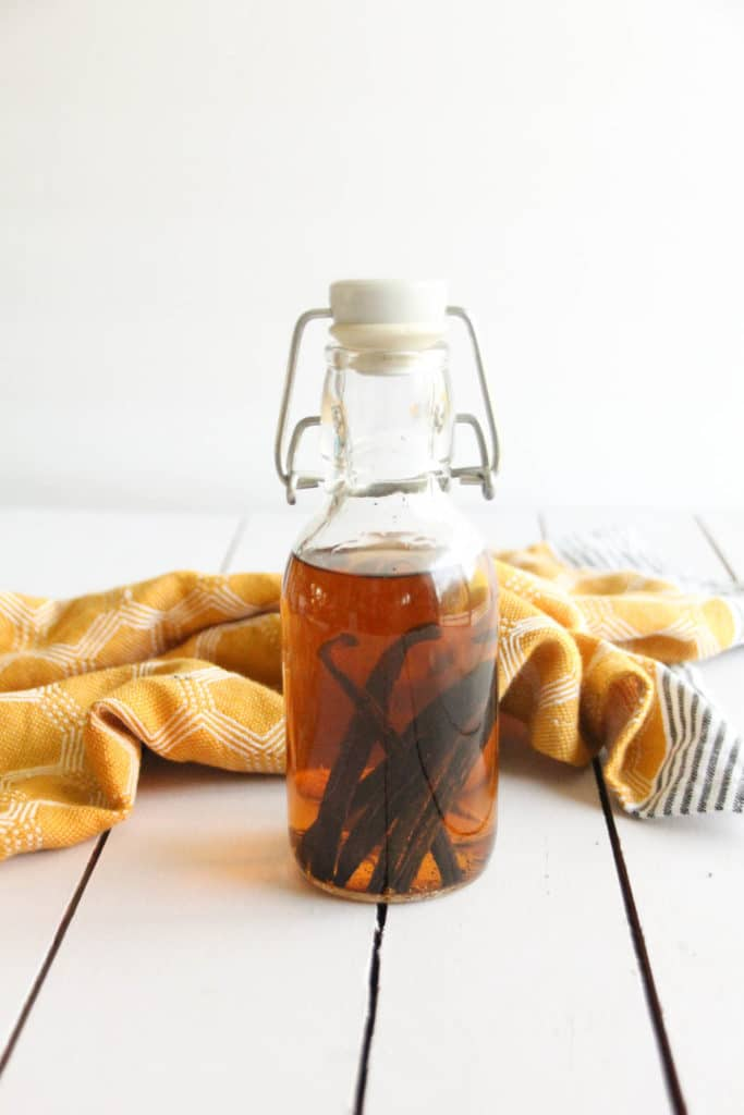 A glass bottle of homemade vanilla extract with vanilla beans in the bottle on a white table