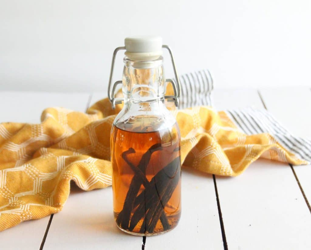 A finished glass bottle of homemade vanilla extract with vanilla beans in the bottle