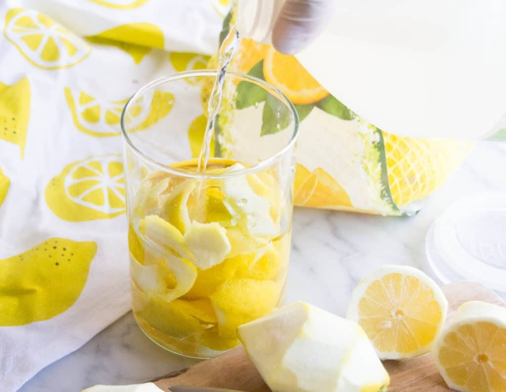 Pouring vinegar into a glass jar filled with fresh lemon peels