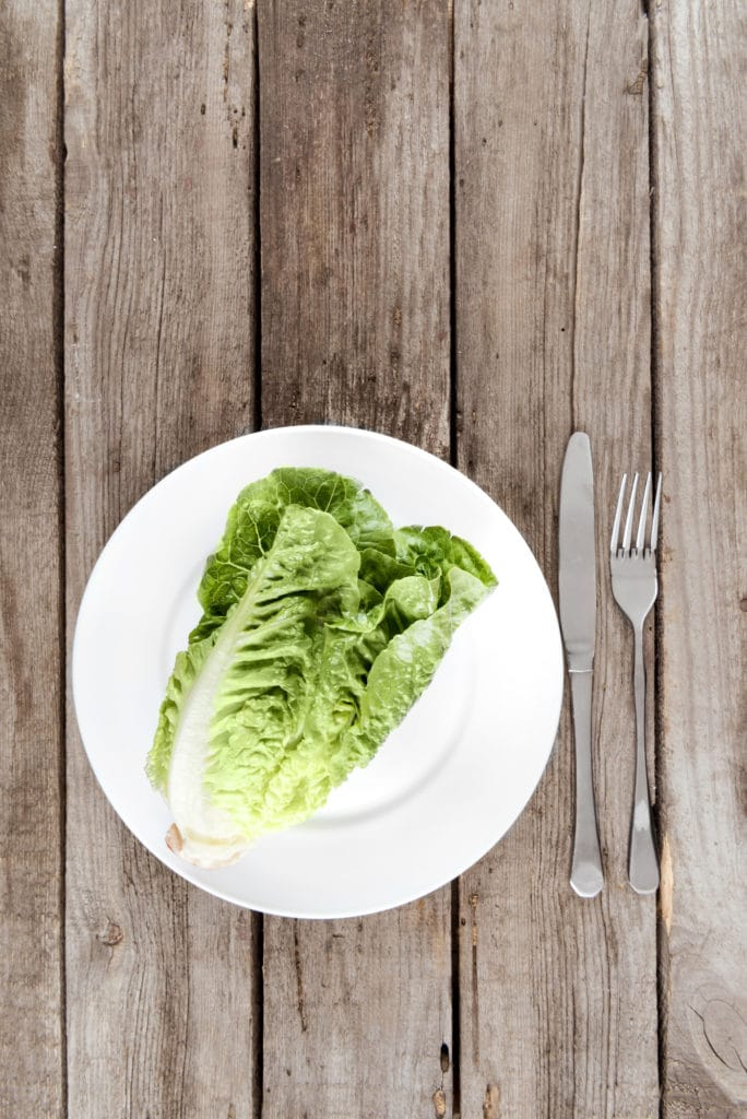 Leaves of lettuce on a white plate on a rustic table