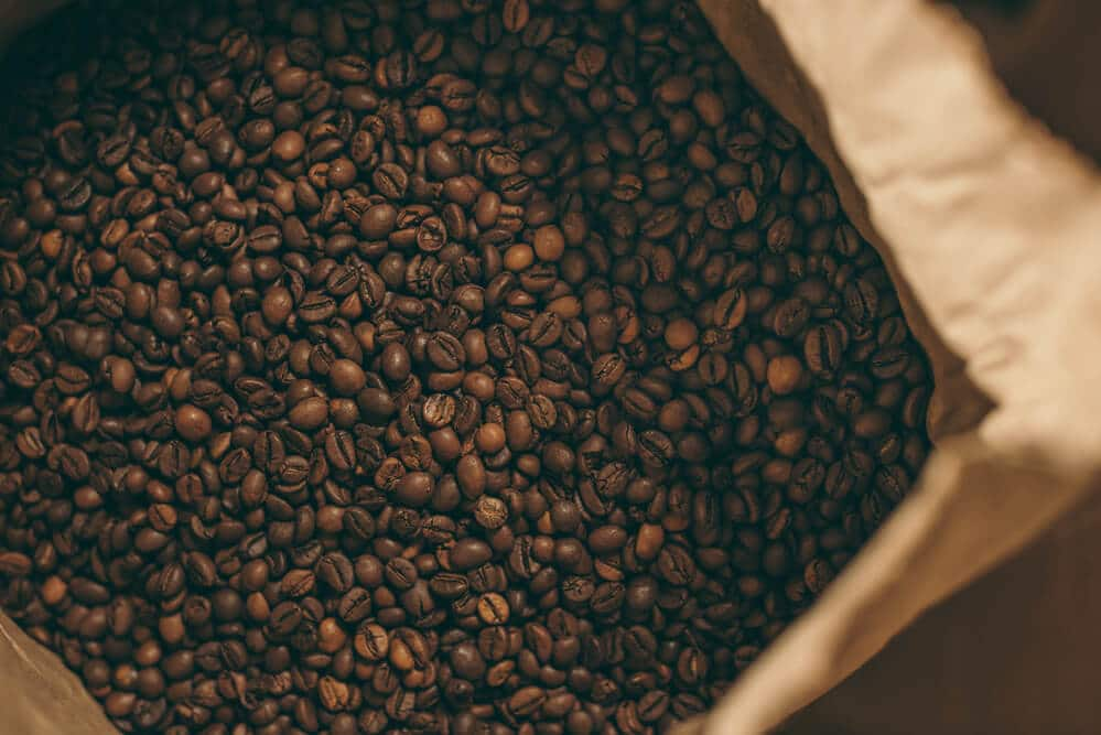 Coffee beans in a brown paper bag