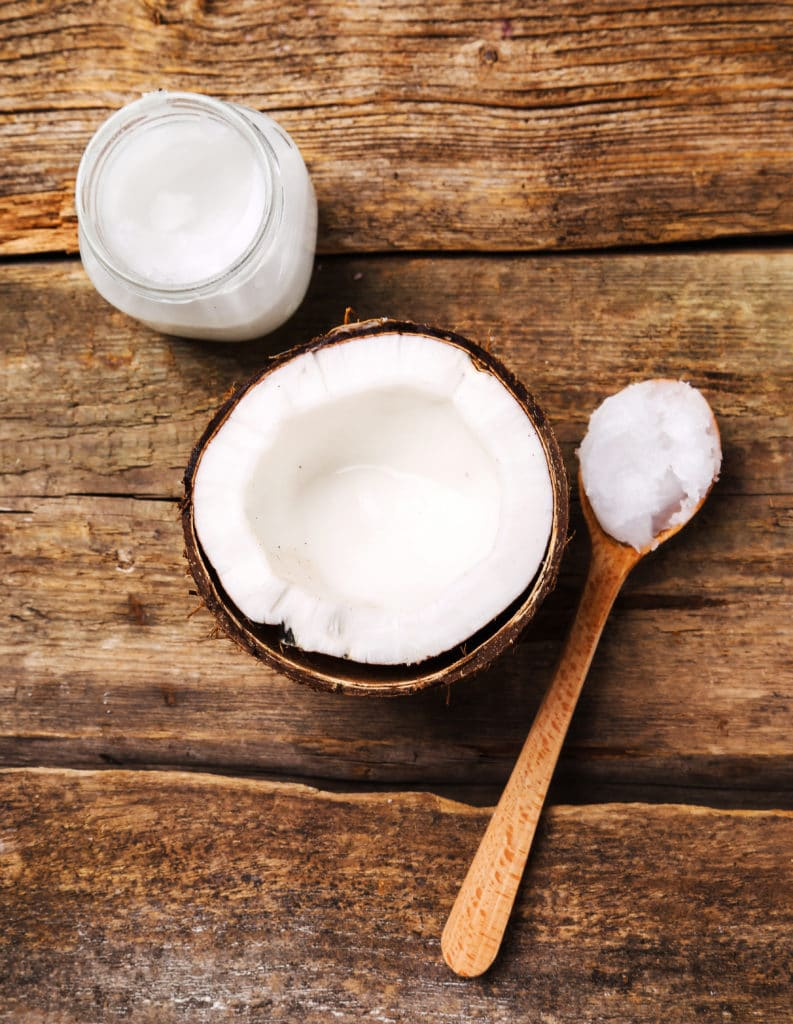An open coconut and a small glass jar of coconut oil on a wooden table