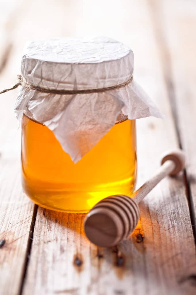 full jar of honey and honey stick on rustic wooden board