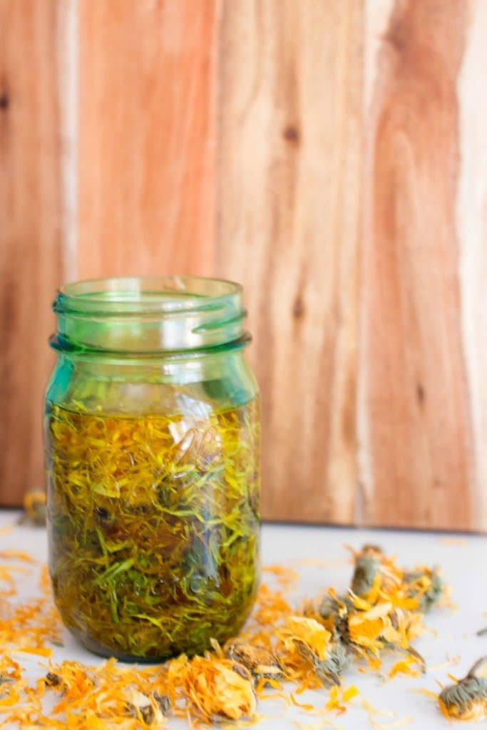 calendula flowers infusing into oil in a green mason jar