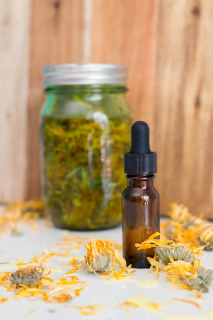a glass jar and a dropper bottle with calendula oil