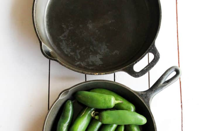 Two cast iron frying pans on a white wood table with green peppers