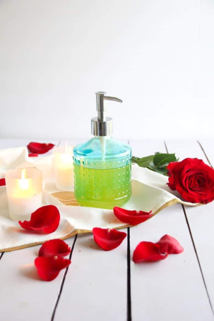 A glass pump bottle of massage oil on a table with a red rose