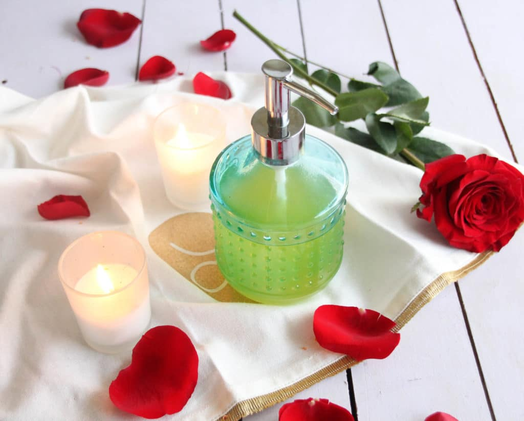 A glass pump bottle filled with massage oil on a table with a candle and a rose