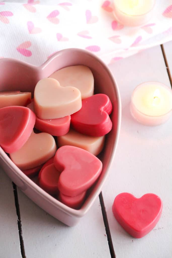 A pink bowl of DIY lotion bar hearts in multiple shades of pink