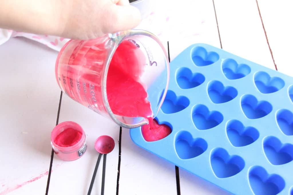 Pouring dark pink liquid lotion bar mixture from a glass measuring cup into heart shaped molds
