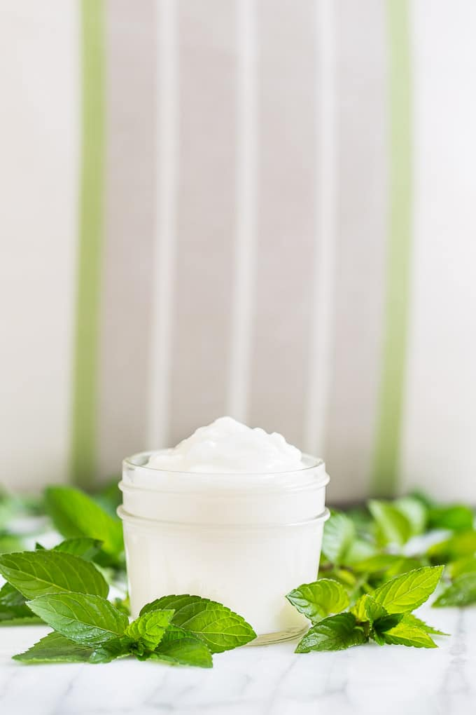 Light and fluffy moisturizer in a glass jar surrounded by fresh mint