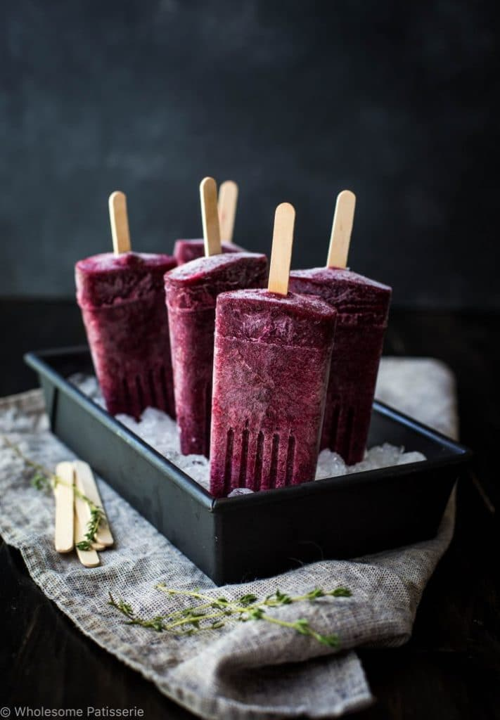 Deep purple kombucha berry popsicles chilling in a pan of ice