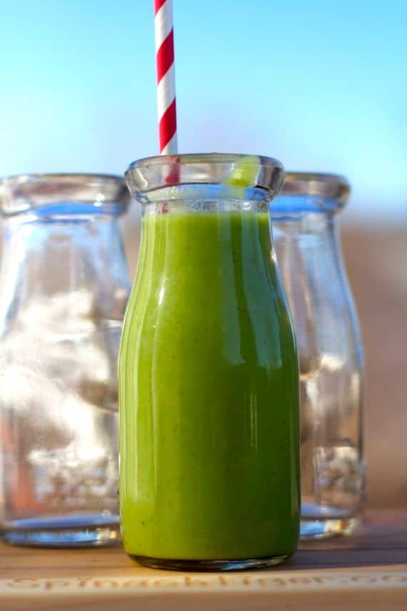 A glass bottle of green kombucha smoothie with a red and white straw