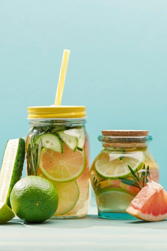 Two glasses of cucumber water filled with slices of citrus and cucumber
