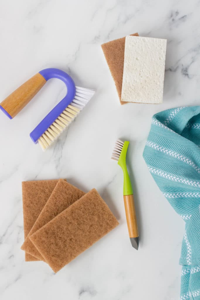 colorful cleaning brushes, sponges, and towels on a marble counter