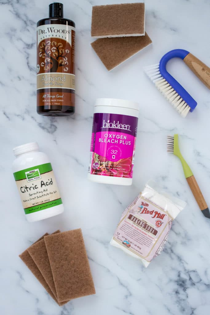 Ingredients and cleaning tools for natural DIY cleaning recipes on a marble counter