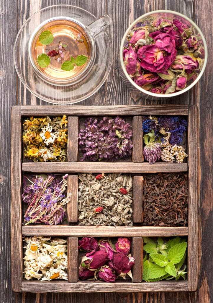 A variety of colorful herbs for tea in a wooden organizer