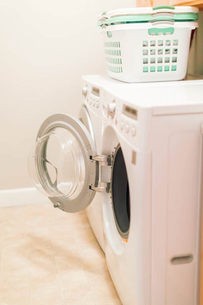 an open washing machine with laundry baskets on top