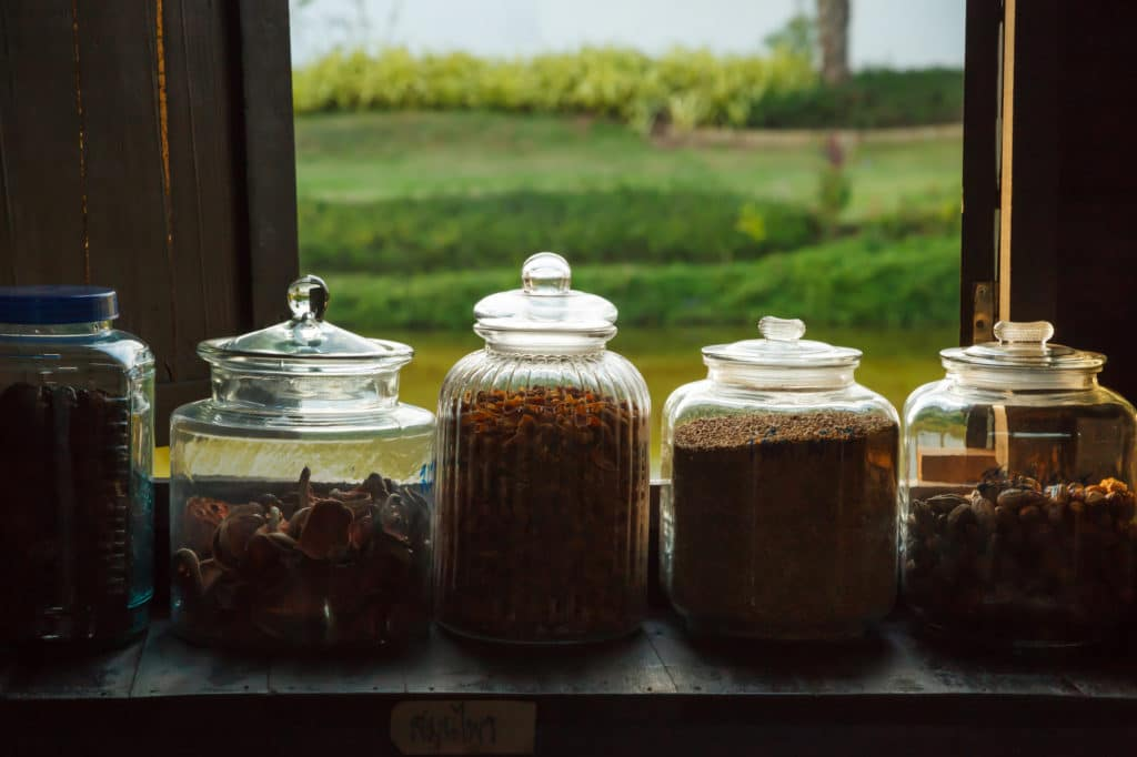 traditional herbs in glass jars in front of a window